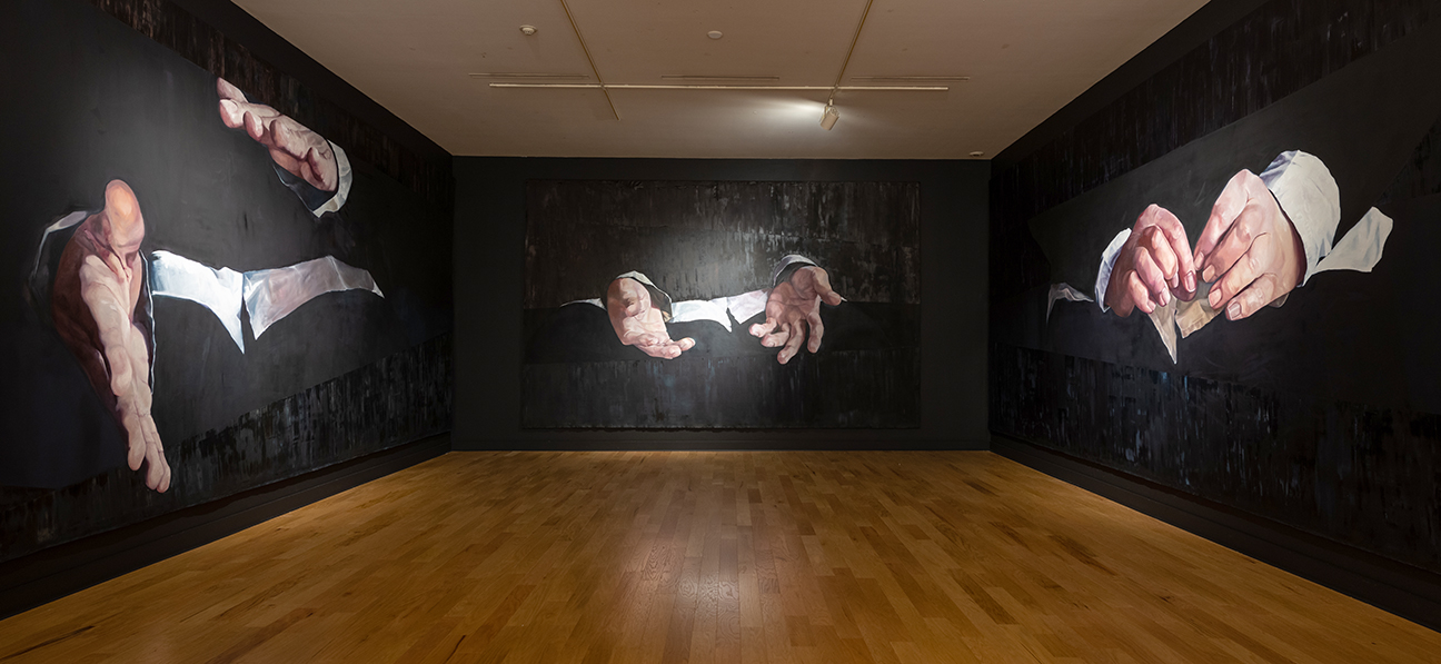 Three visible walls are painted black, each wall has a set of hands that take up most of each wall.