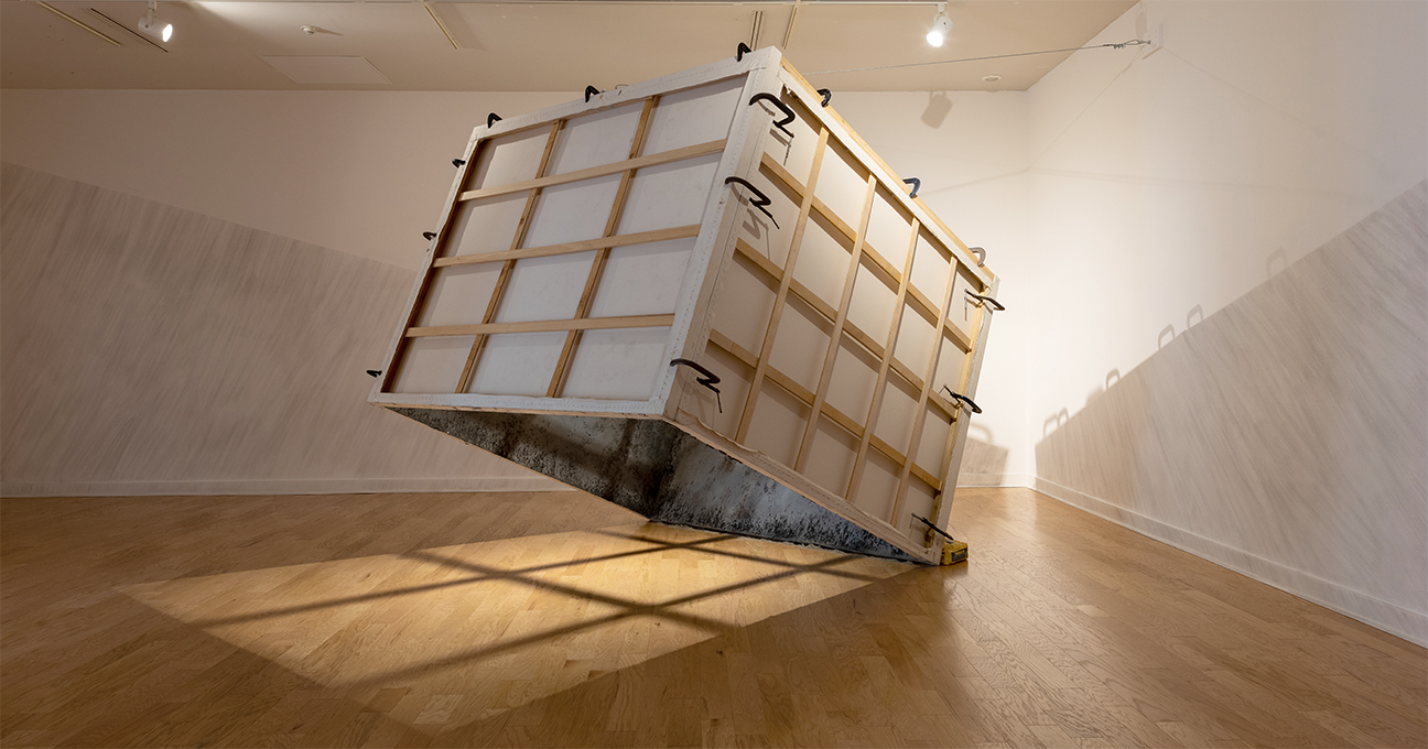 A shipping crate suspended in the air with a shadow being cast though it in a gallery.